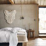 spálňa v neutrálnych odtieňoch, s betónovou stenou, závesnou makramé dekoráciou, drevenou posteľou a bielymi obliečkami