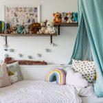 biela posteľ v detskej izbe s nebesami a otvorenými poličkami na stene
