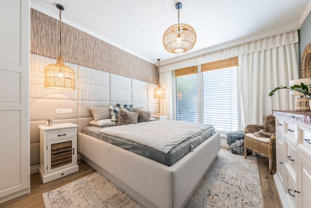 vidiecka spálňa v neutrálnych farbách s ratanovým kreslom, bielou komodou, tkaným kobercom, bielymi stolíkmi, čalúnenou posteľou a čalúneným čelom postele, ktoré sa tiahne po celej dĺžke steny