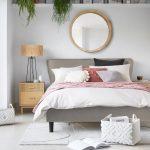 spálňa si sivou posteľou, okrúhlym zrkadlom, dreveným nočným stolíkom a nástennou policou pod stropom