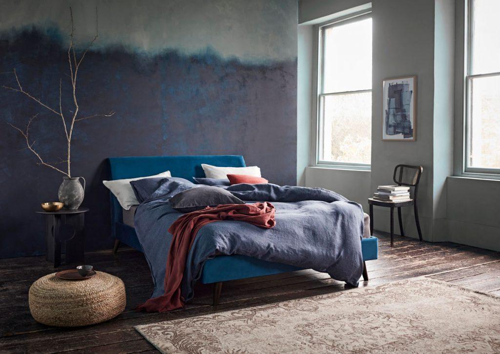 spálňa s atramentovou ombré maľovkou a modrou posteľou s modrými a červenými textíliami