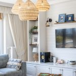 detail obývačka s prírodnými vypletanými lampami, bielou obývačkovou stenou a sivou sedačkou