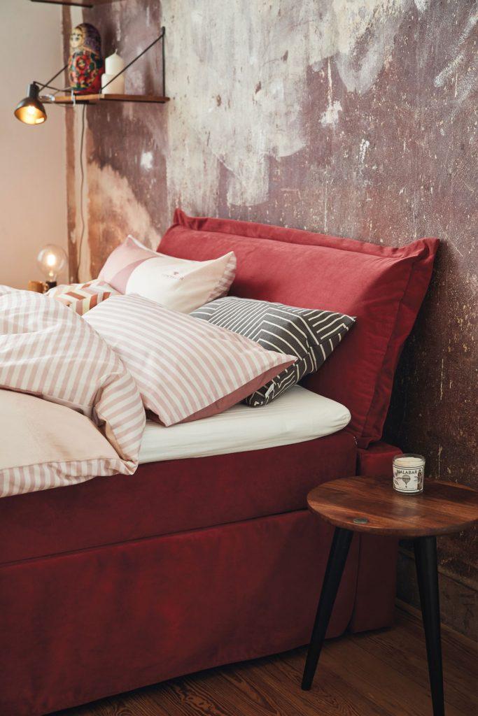 spálňa s červenou čalúnenou posteľou a tapetou s ošúchaným vzhľadom steny