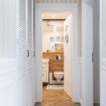 pohľad do kúpeľne z chodby s bielymi skriňami a hnedou dlažbou súvisle vedúcou až do kúpeľne