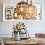 jedálenský drevený stôl s čalúnenými stoličkami, vázou a etažérom a prútenými svietidlami