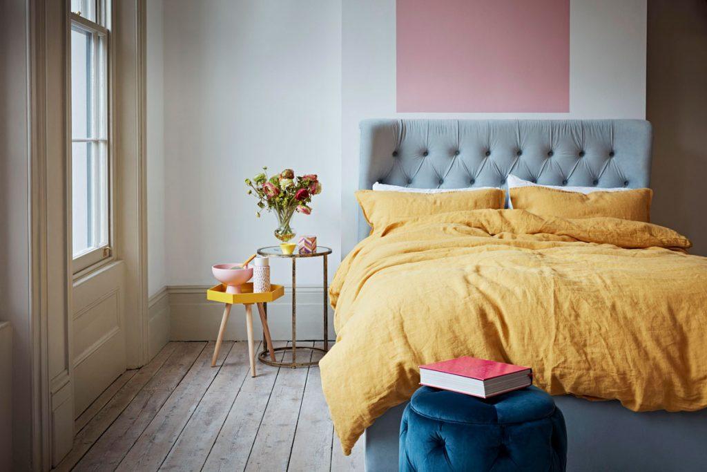 pestrofarebná spálňa s čalúnenou sivou posteľou, žltými obliečkami, modrým pufom a stenou s geometrickým vzorom