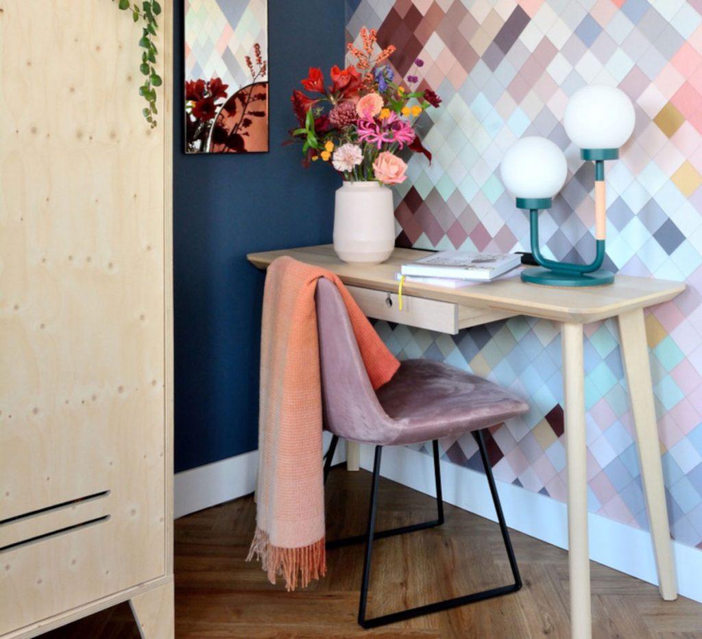 pracovný kútik v spálni s nástenným stolíkom, zamatovou fialovou stoličkou, modrou lampou a farebnou geometrickou tapetou