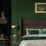 Spálňa s tmavozelenou stenou, zlatými stolíkmi, svietidlom a lampou a sivou čalúnenou posteľou